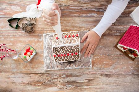 decoracion de pasteles: la cocina, la gente, la Navidad y la decoración concepto - cerca de feliz mujer haciendo casas de jengibre en casa