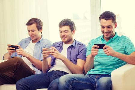 hang out: friendship, technology and home concept - smiling male friends with smartphones at home