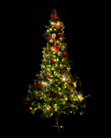 winter, holidays, decoration and illumination concept - beautiful decorated and illuminated christmas tree over black background Banco de Imagens
