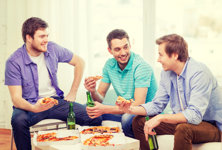 junk: friendship, food and leisure concept - smiling male friends with beer and pizza hanging out at home