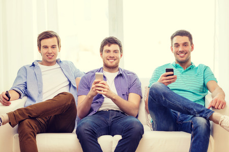 room mate: friendship, technology and home concept - smiling male friends with smartphones at home