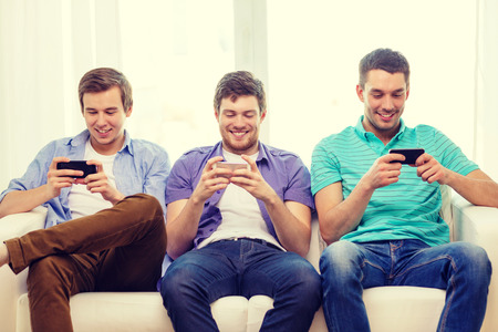 man looking out: friendship, technology and home concept - smiling male friends with smartphones at home