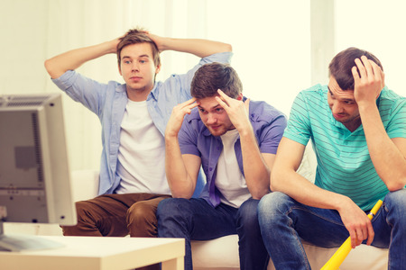 vuvuzela: friendship, sports and entertainment concept - sad male friends with vuvuzela watching sports on tv at home Stock Photo