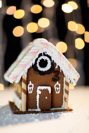 sugarcoated: holidays, christmas, baking and sweets concept - closeup of beautiful gingerbread house on table over black garland lights