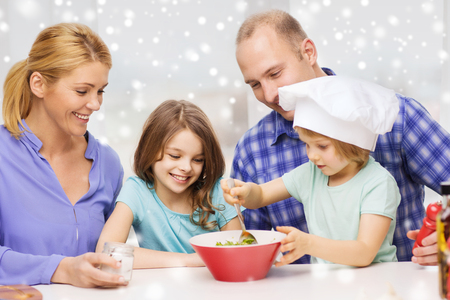 a little dinner: food, family, children, happiness and people concept - happy family with two kids making salad for dinner at home Stock Photo