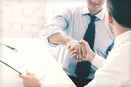 レッソンとオフィス コンセプト - オフィスで握手 2 人のビジネスマン