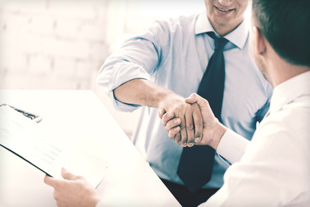 businessman smiling: businesss and office concept - two businessmen shaking hands in office