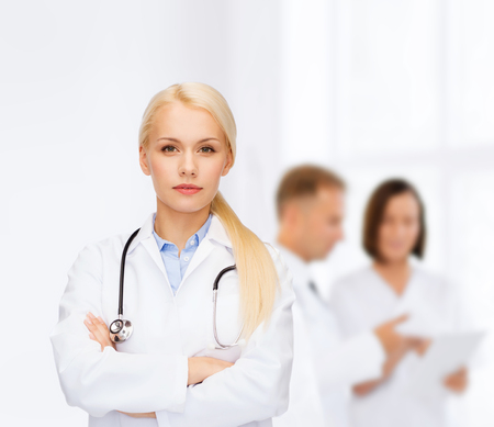 serious doctor: healthcare and medicine concept - serious female doctor with stethoscope
