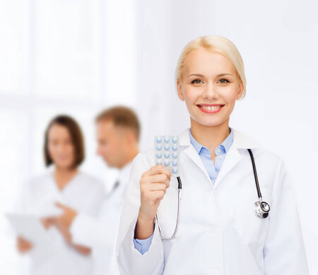 painkiller: healthcare, medicine and pharmacy concept - smiling female doctor and with pills and stethoscope