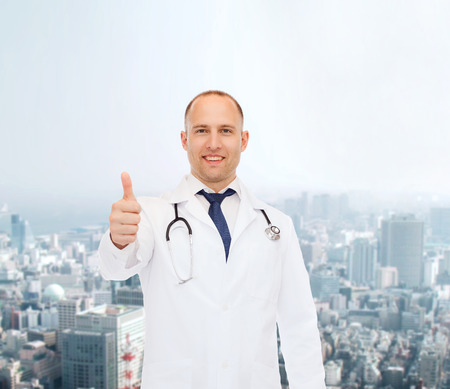 approvement: healthcare, profession, gesture and medicine concept - smiling male doctor with stethoscope showing thumbs up over city background