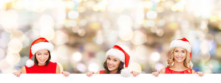 christmas, x-mas, people, advertisement and sale concept - happy women in santa helper hat with blank white board over lights background photo