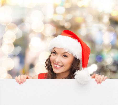 christmas, x-mas, people, advertisement and sale concept - happy woman in santa helper hat with blank white board over lights background photo