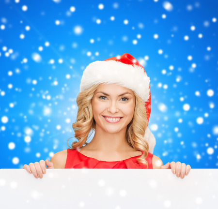 christmas, x-mas, people, advertisement and sale concept - happy woman in santa helper hat with blank white board over blue snowy background photo