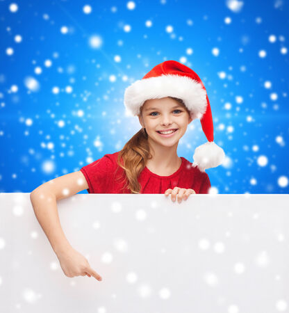 christmas, holidays, people, advertisement and sale concept - happy little girl in santa helper hat with blank white board over blue snowy background photo
