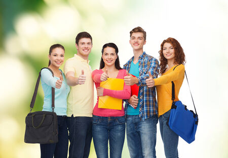 thumbs up group: friendship, education, ecology and people concept - group of smiling teenagers with folders and school bags showing thumbs up over green background