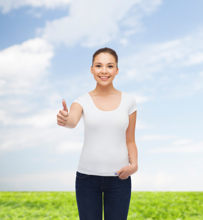 approvement: advertising, summer vacation, gesture and people concept - smiling young woman in blank white t-shirt showing thumbs up over natural background Stock Photo