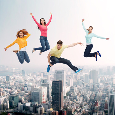 air jump: happiness, freedom, friendship, movement and people concept - group of smiling teenagers jumping in air over city background Stock Photo