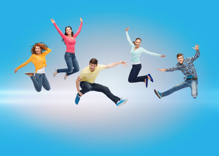 hand movements: happiness, freedom, friendship, movement and people concept - group of smiling teenagers jumping in air over blue laser background Stock Photo