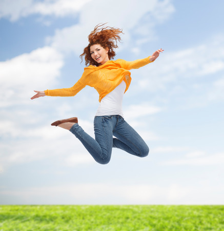 happiness, freedom, movement and people concept - smiling young woman jumping high in air over green background over blue sky and grass background Stock Photo