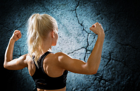 sportive: fitness, sport and people concept - sporty woman flexing and showing biceps form back Stock Photo