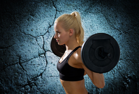 good: fitness, sport, powerlifting and people concept - sporty woman exercising with barbell over concrete wall background Stock Photo