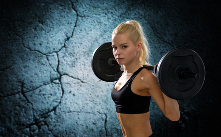 powerlifting: fitness, sport, powerlifting and people concept - sporty woman exercising with barbell over concrete wall background Stock Photo
