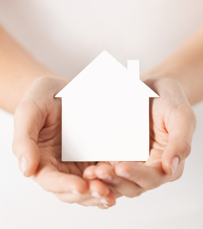 real estate and family home concept - closeup picture of female hands holding white blank paper house photo