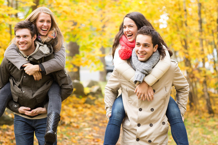 fall fun: love, friendship, family and people concept - smiling friends having fun in autumn park