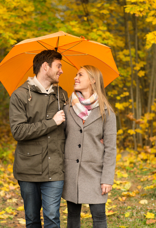 walking in the rain: love, relationship, season, family and people concept - smiling couple with umbrella walking in autumn park