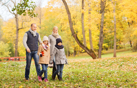 family walking: family, childhood, season and people concept - happy family in autumn park Stock Photo