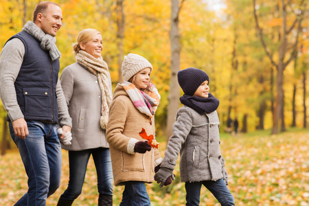 family, childhood, season and people concept - happy family in autumn park photo