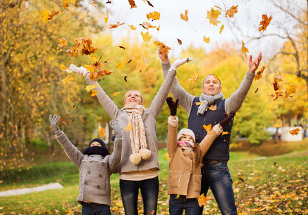leaf: family, childhood, season and people concept - happy family playing with autumn leaves in park