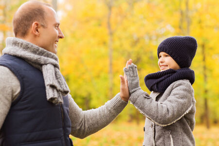 high park: family, childhood, season, gesture and people concept - happy father and son making high five in autumn park
