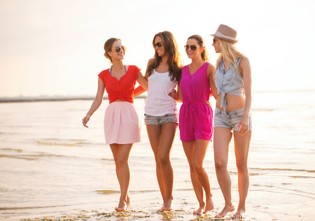 friends party: summer vacation, holidays, travel and people concept - group of smiling young women in sunglasses and casual clothes on beach