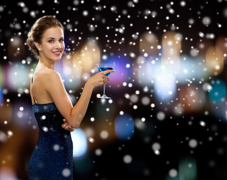 cocktail party: party, drinks, holidays, christmas and people concept - smiling woman in evening dress holding cocktail over night lights and snow