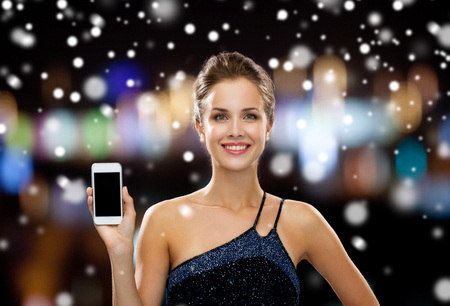 holiday lights display: technology, christmas, holidays, advertising and people concept - smiling woman in evening dress holding smartphone over night lights and snow