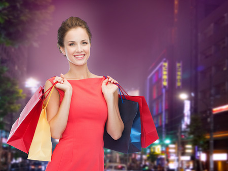 night life: happiness, consumerism, sale and people concept - smiling young woman with shopping bags over night city background Stock Photo