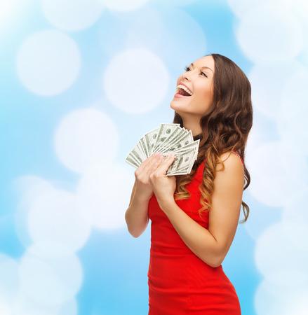 navidad, días de fiesta, la venta, la banca y la gente concepto - mujer sonriente en vestido rojo con nosotros el dinero del dólar sobre las luces de fondo azul