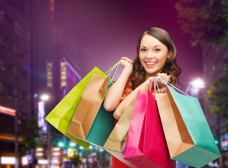 consumerism: happiness, consumerism, sale and people concept - smiling young woman with shopping bags over night city background Stock Photo
