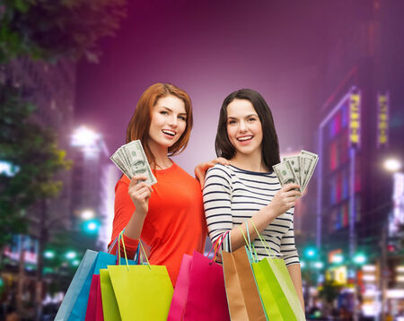 sale, friendship and people concept - two smiling teenage girls with shopping bags and cash money over night city background photo