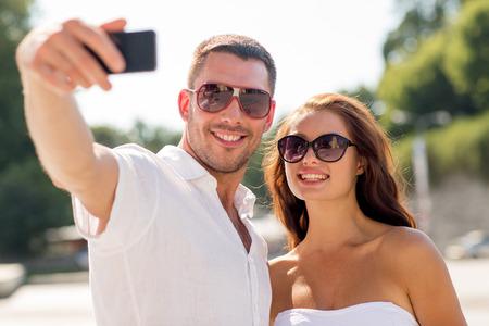 haciendo el amor: amor, boda, verano, las citas y las personas concepto - sonriente pareja con gafas de sol abrazando y haciendo Autofoto con el tel�fono inteligente en el parque Foto de archivo