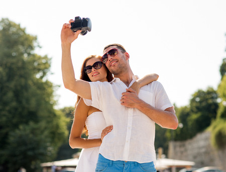 love, wedding, summer, dating and people concept - smiling couple wearing sunglasses making selfie with digital camera in park