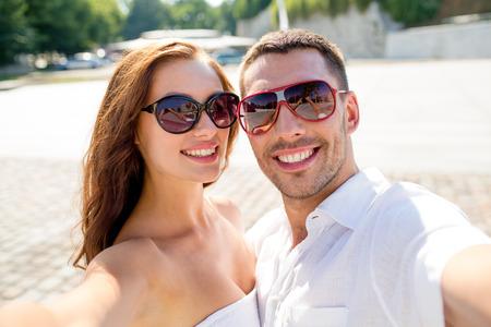 haciendo el amor: amor, boda, verano, las citas y las personas concepto - sonriente pareja con gafas de sol que hacen Autofoto en la ciudad