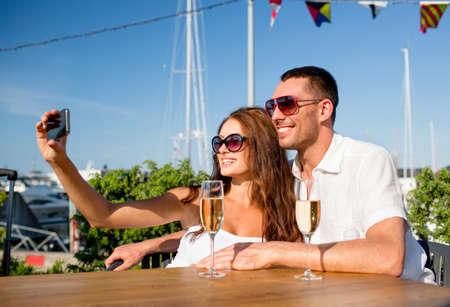 haciendo el amor: amor, citas, personas y concepto de vacaciones - sonriente pareja con gafas de sol bebiendo champ�n y haciendo Autofoto en el caf�
