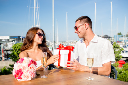 love, dating, people and holidays concept - smiling couple wearing sunglasses sitting with gift box, flowers and champagne at cafe photo