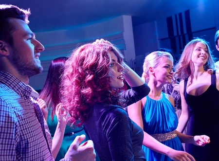 party, holidays, celebration, nightlife and people concept - smiling friends dancing in club photo
