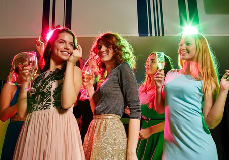 party, holidays, celebration, nightlife and people concept - smiling friends with glasses of champagne dancing in club photo