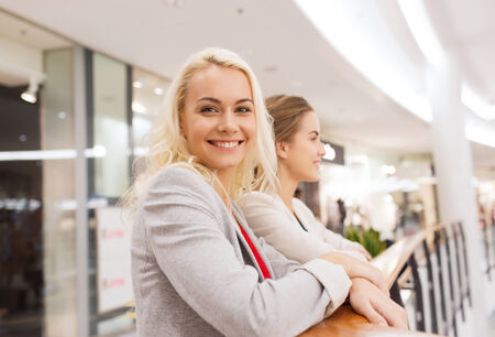 consumerism: sale, consumerism and people concept - happy young women in mall or business center Stock Photo