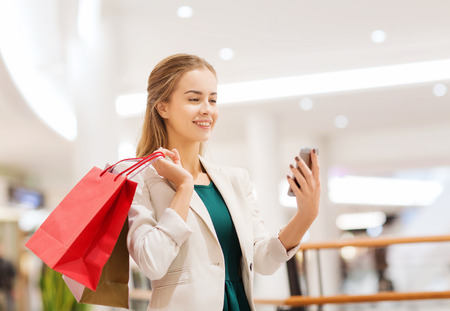 sale, consumerism, technology and people concept - happy young woman with smartphone and shopping bags taking selfie in mall photo