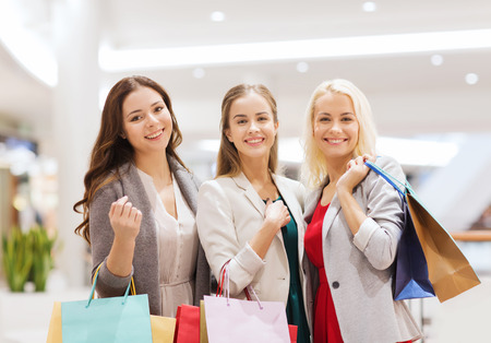 sale, consumerism and people concept - happy young women with shopping bags in mall photo